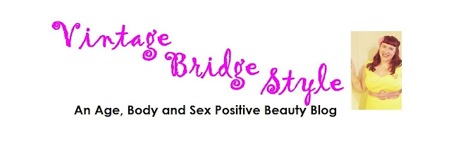Bridget Eileen beauty blog Vintage Bridge Style an age body and sex positive beauty blog banner with white background, pink and black scrpt and a picture of Bridget Eileen in a yellow 50s style dress and red hair in victory rolls