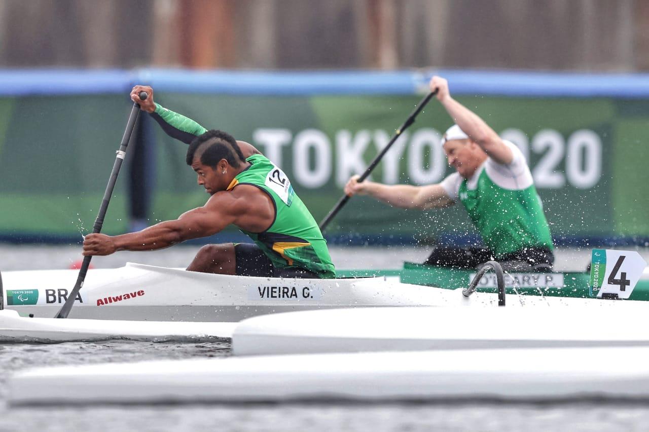 Giovane Vieira de Paula está em primeiro plano, remando, ajoelhado na canoa, com o cabelo parcialmente raspado