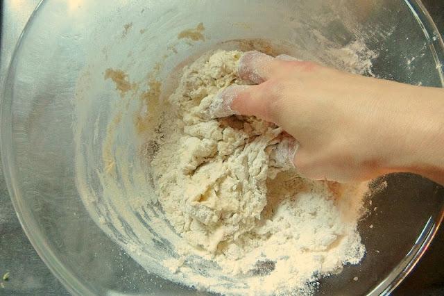 中華まんの生地材料をボウルで混ぜ合わせ、ぬるま湯を少しずつ注いでこねます