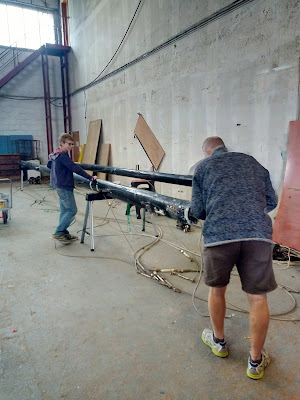 Man and child in hangar working on masts