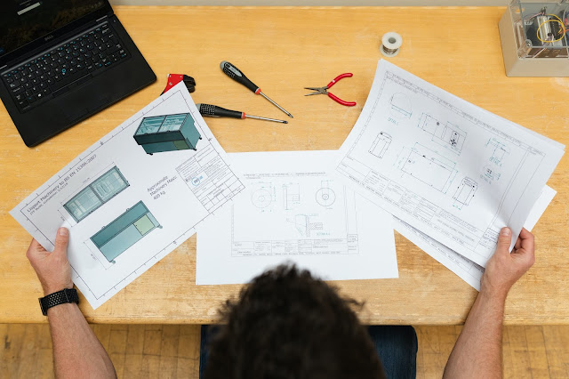 From above: A person sitting at a desk perusing instructions and blueprints to build something