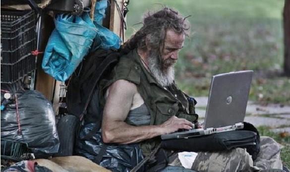 Hombre sin techo con una laptop
