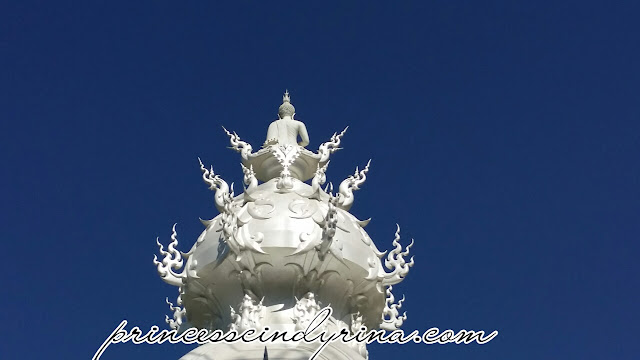 Buddha statue on the peak of white temple
