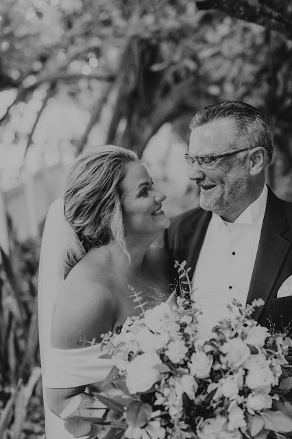 Candid laughs between bride and father in outdoor setting.