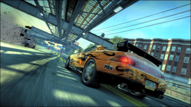 """سيارة رياضية صفراء تقود على طريق سريع تحت ممر علوي في """"Burnout Paradise Remastered""""."""