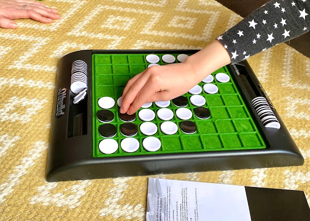 Close up of the Othello game board and a child's hand turning pieces over.