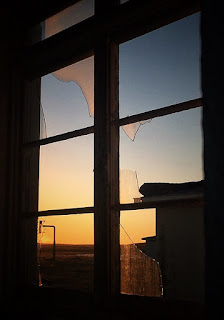 Sunset in Puerto Percy ghost town through the broken panes of glass.