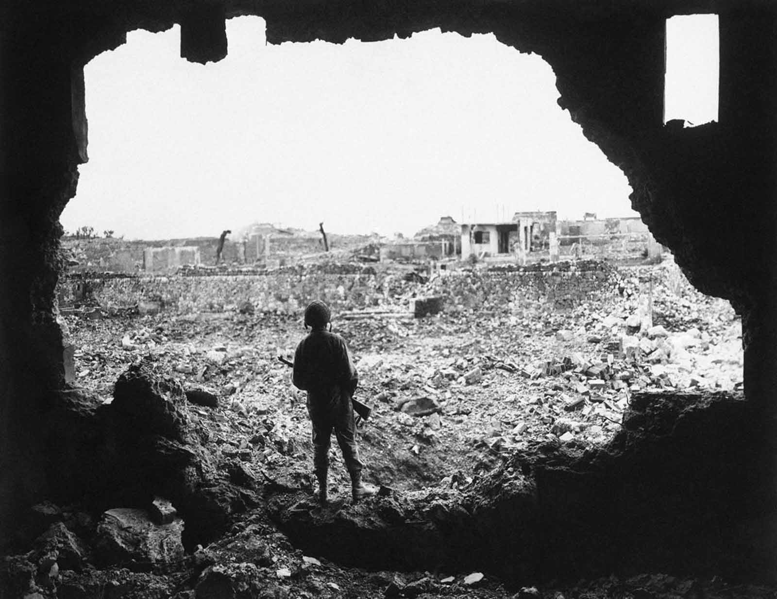 Perched on the rim of a gaping hole in the wall of a theater in the Ryukyu capital, a Marine rifleman views the result of the American bombardment of Naha, Okinawa, Japan, on June 13, 1945. Structure skeletons are all that remain of the city with a pre-invasion population of 443,000 people.