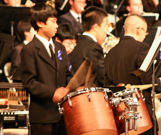 boy playing tom tom drums in orchestra