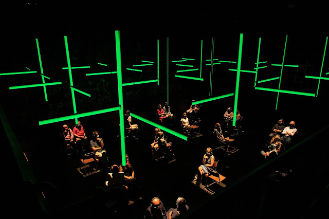 A photo taken from a high angle. Long thin cylinders of light hang over the space, illuminated in green. Below, pairs of chairs are spaced out on the floor, each pair illuminated in white light. Theatre patrons are sitting in most of the chair, each wearing a pair of headphones.