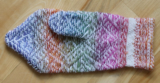 Hand knit colorwork wool mitten turned inside out on a light wood background.