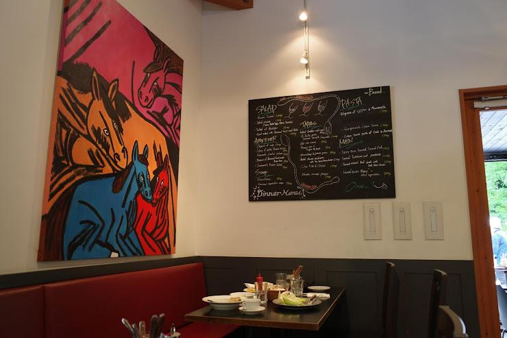 壁に大きな絵とメニューが掛けられたベーカリー&レストラン沢村の店内2