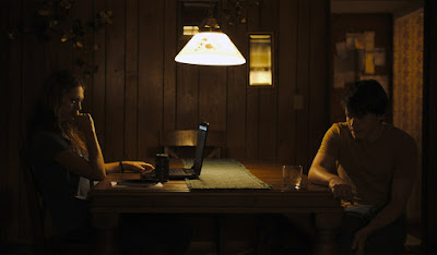 Movie scene from the 2019 drama film Light from Light where Marin Ireland and Josh Wiggins sit at a table and talk together about her job as a paranormal investigator