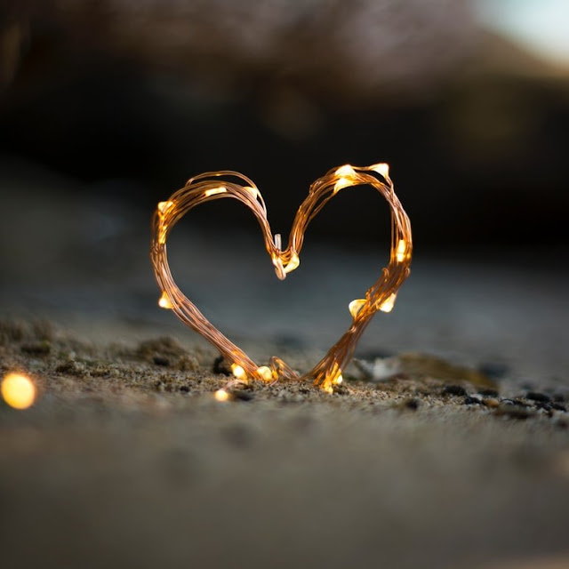 String lights shaped into a heart and placed in the sand
