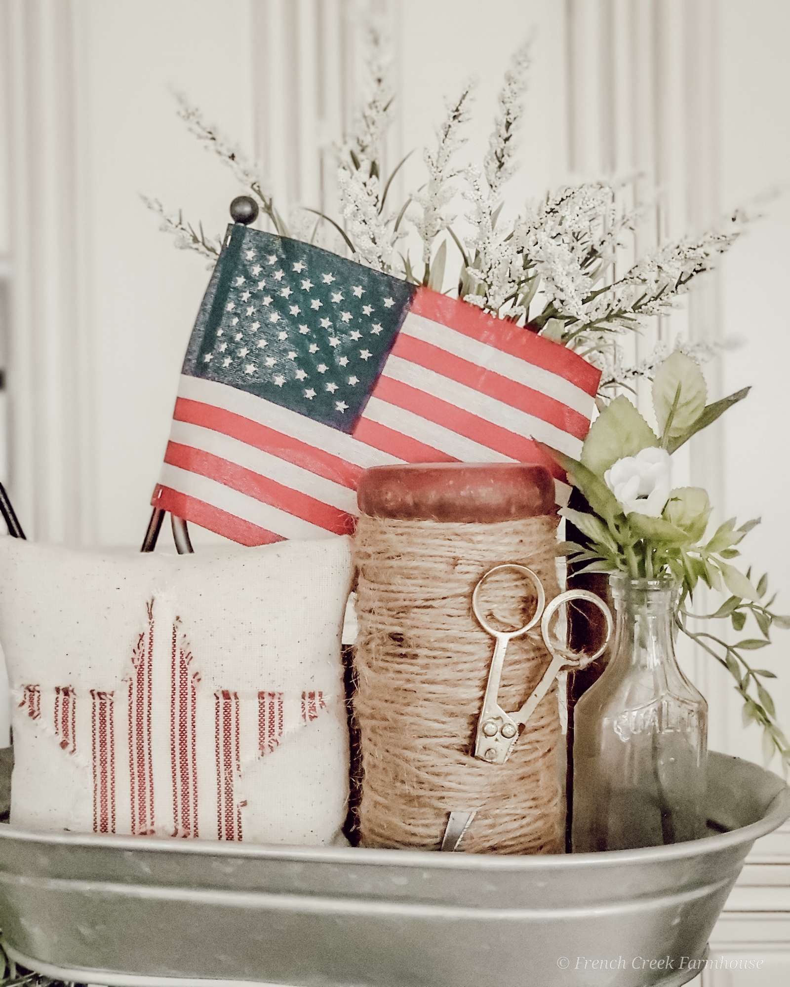 A vintage wooden spool and American flag decor