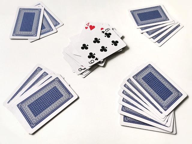na zdjęciu widać cztery zestawy kart każdego z graczy a na środku stołu stos wyrzuconych kart-par