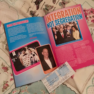 Hairspray programme opened to blue and pink double spread page reading 'Integration not Segregation'