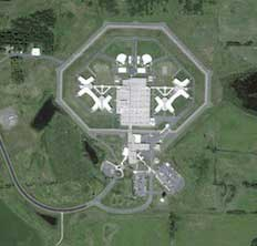Aerial view of a prison with symmetrical buildings for eyes and a border fence shaped like a skull