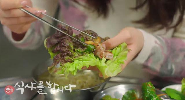 se ve como colocan la carne cocinada con briquetas con palillos sobre una hoja de lechuga para envolverla