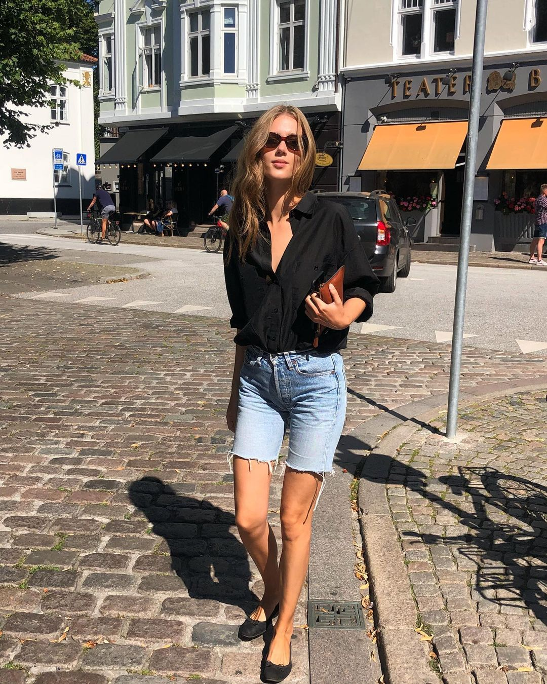 How to Wear Denim Bermuda Shorts — Cecilie Moosgaard Nielsen spring or summer outfit idea with a balck button-down shirt, wallet clutch bag, and black ballet flats