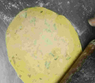 Rolling Missi roti with a roller pin