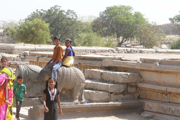 Siblings ride a rock elephant at the ruins of Hampi, Karnataka, India
