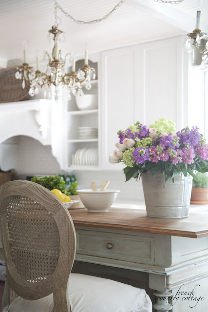 french cottage style kitchen island with a bucket of flowers
