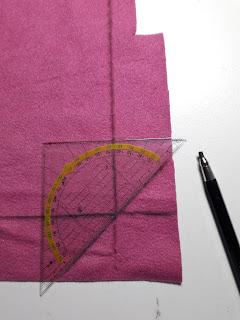 Zo leg je de geodriehoek op de stof. Net als de foto hierboven.