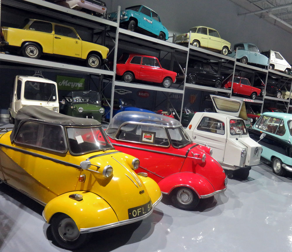 Microcars displayed on steel shelving.