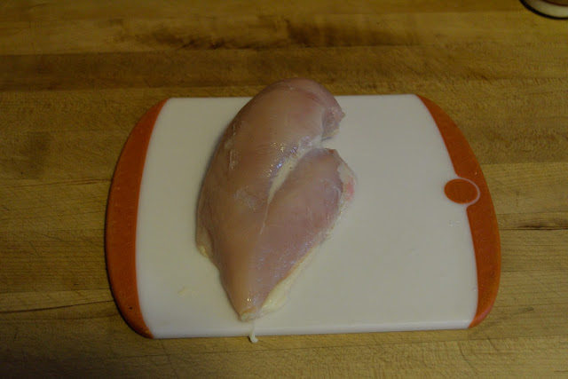 a chicken breast, on a cutting board.
