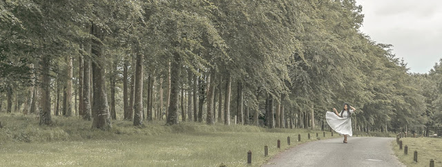 girl in white dress walks along road bordered by tall green trees