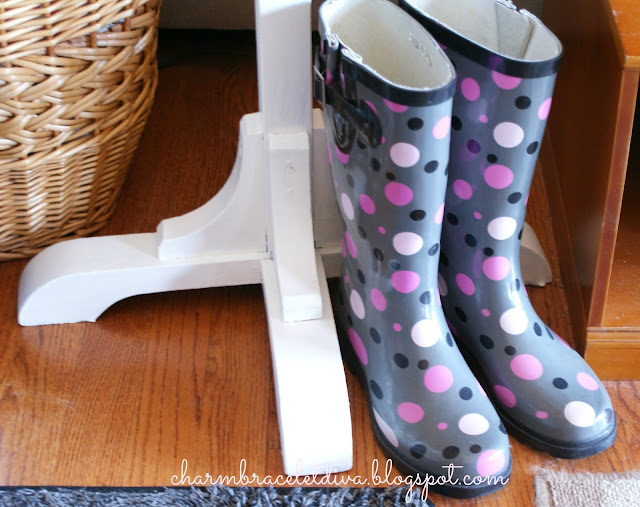 Bottom of wooden coat rack and a pair of polka dot wellies