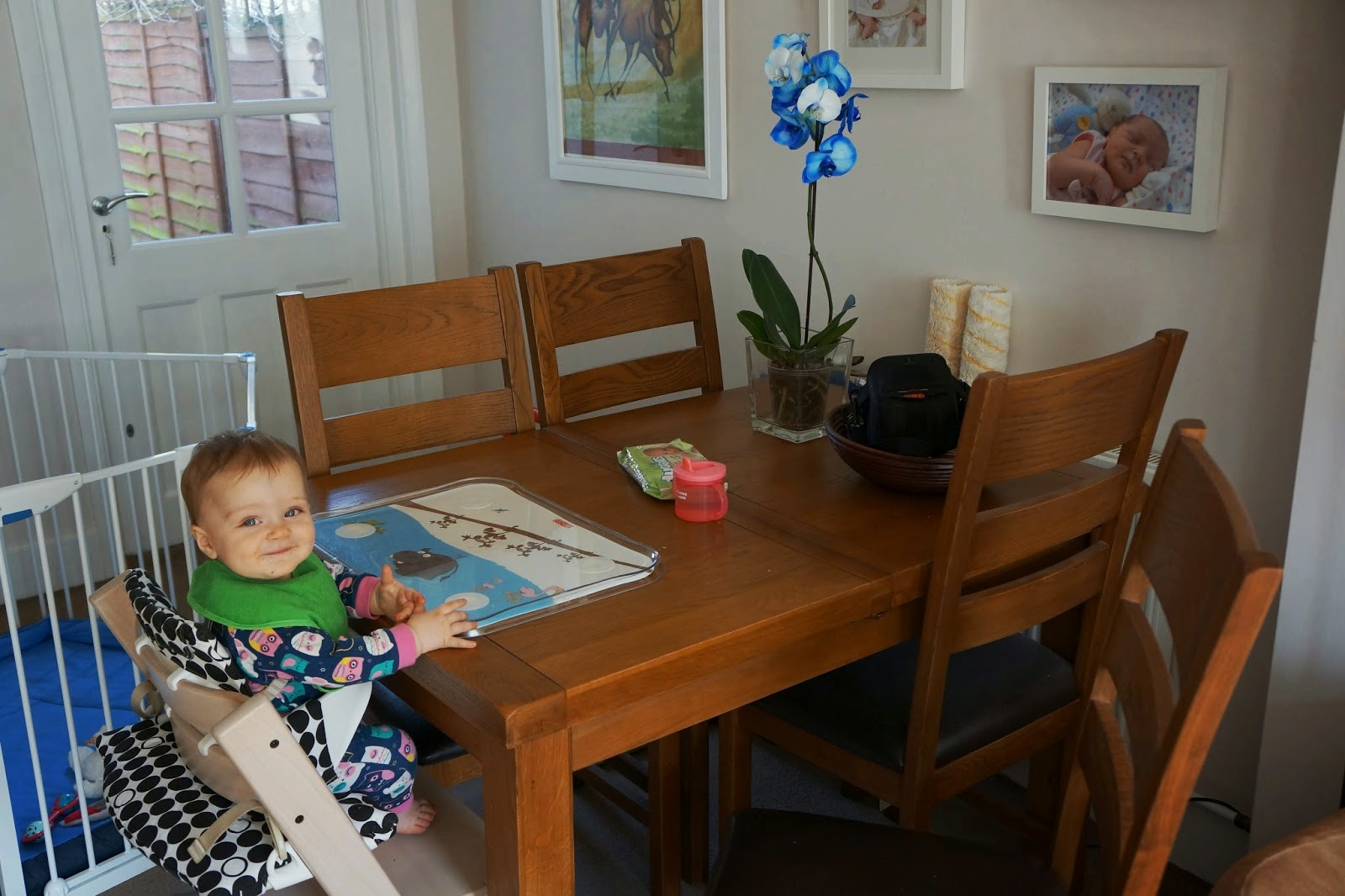 child sitting at a table on stokke tripp trapp chair