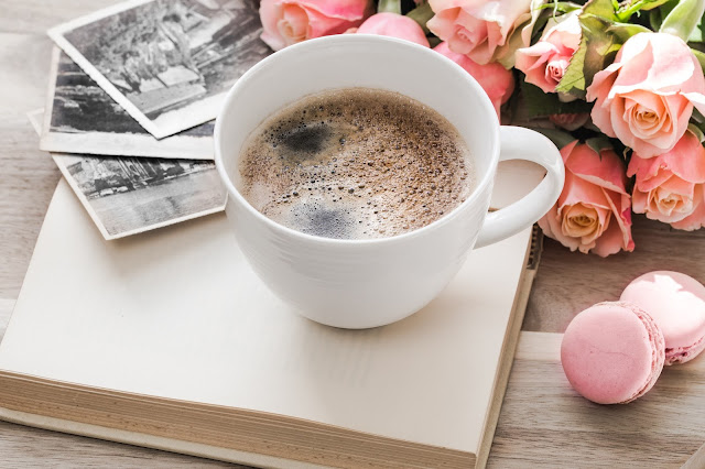 There is a white coffee mug with black coffee inside. The mug is resting on an open book with flowers surrounding it. There are also 3 pink macaroons in the bottom right corner and polaroid photos in the top left.