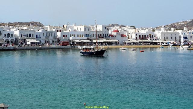 Grecki morze z małą łódką na powierzchni w tle greckie białe domki miasta Mykons