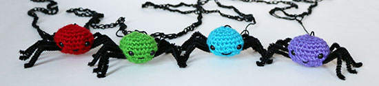 Four amigurumi spiders lined up on a white background. Each has a different colored body - red, green, blue, purple - with black pipe cleaner legs and black crocheted web.
