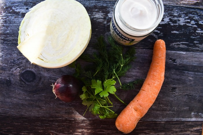 Ingredients to make carrot coleslaw - white cabbage, carrot, dill, parsley & mayo