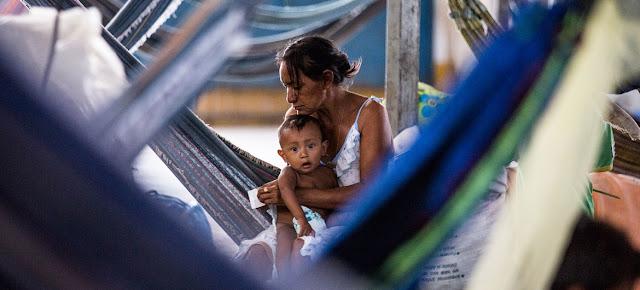 Una madre cuida de su bebé dentro de un gimnasio que se ha convertido en un asentamiento de refugiados en Pintolandia, en el Estado brasileño de Roraima, fronterizo con Venezuela.ACNUR/Vincent Tremeau