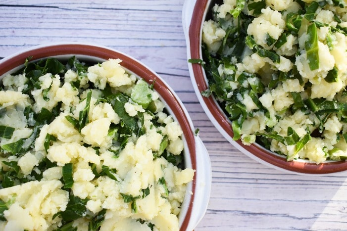 Spring greens mashed potato piled onto individual sausage bakes
