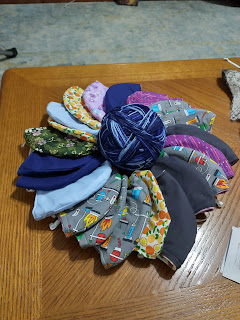 Picture of a fabric masks encircling a ball of blue yarn