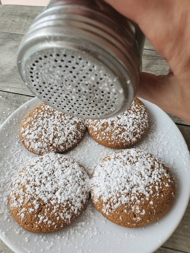these are 4 cookies on a white plate with powdered sugar on top