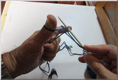 Foto mostrando a agulha de tricô pegando o laço feito no polegar para a montagem à italiana da base de pontos do tricô