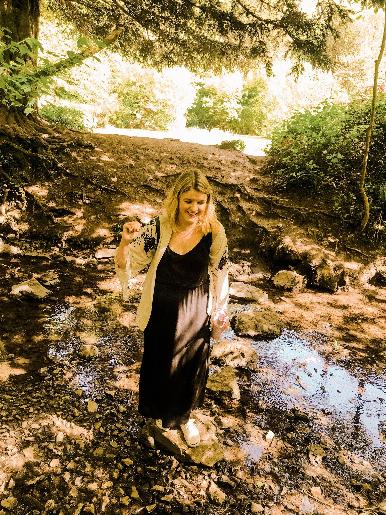 Blogger Chloe Harriets making her way across stepping stones to the other side of the woods - Blaise Castle Bristol