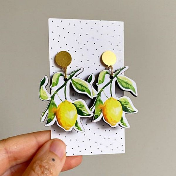 pair of paper earrings on card feature printed lemons, leaves, and gold findings