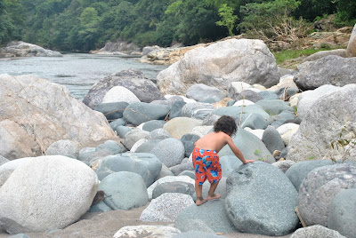 Little boy walking on large rocks next to a river.