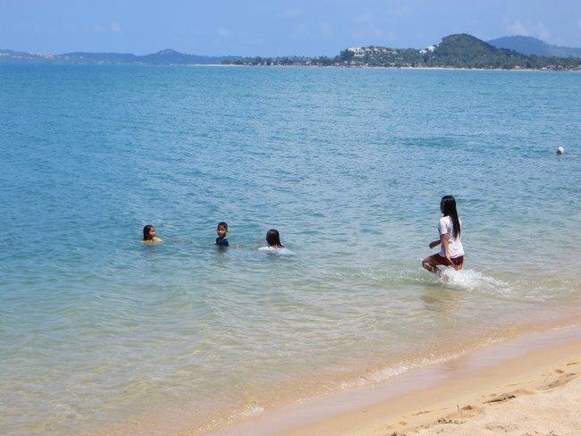 Тайская девушка и дети купаются в одежде