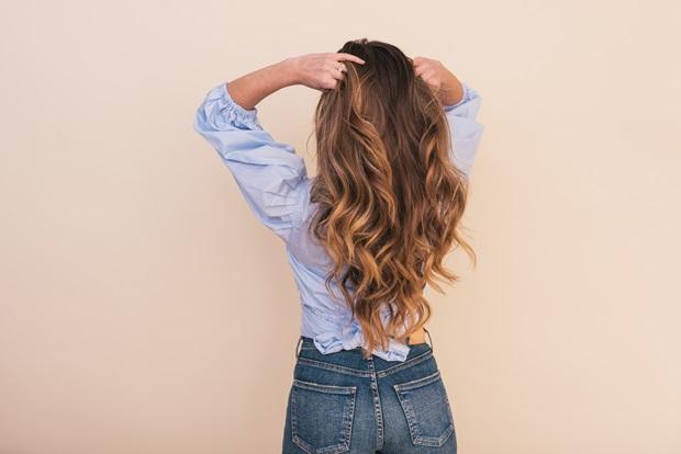 Mulher loira de costas mexendo nos cabelos fortes, saudáveis e hidratados