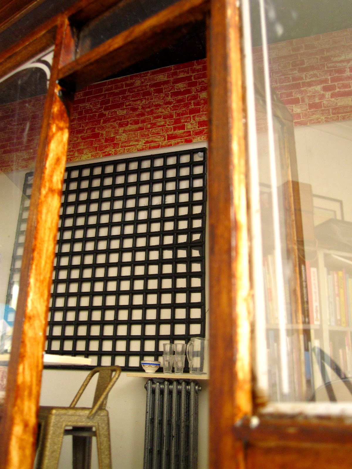 Interior view of a modern dolls' house miniautre cafe, showing a black ceiling made of distressed boards and brick walls below it.