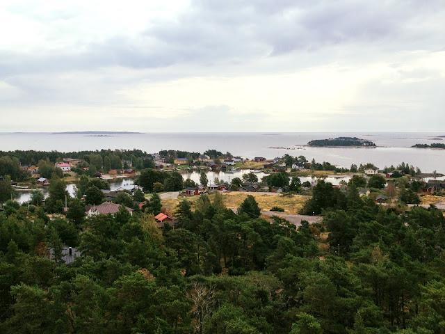 Merimaisema saarineen ja horisontteineen, saaressa mökkejä ja veneitä