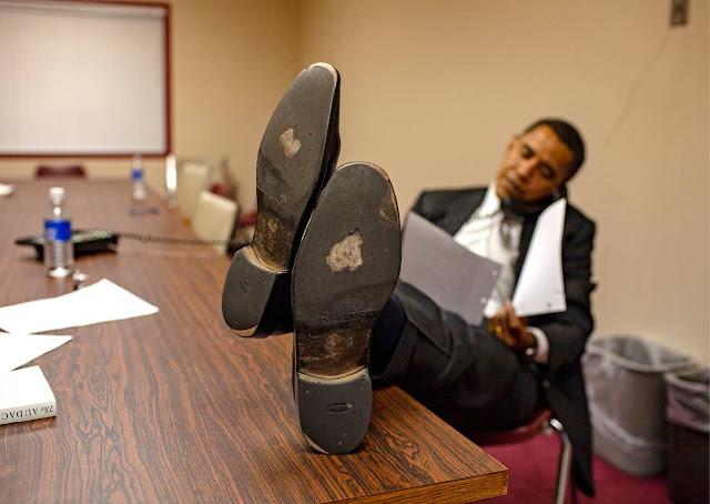 Barak obama siedzi na fotelu z nogami na biurku w butach o mocno zniszonych chodzeniem podeszwach